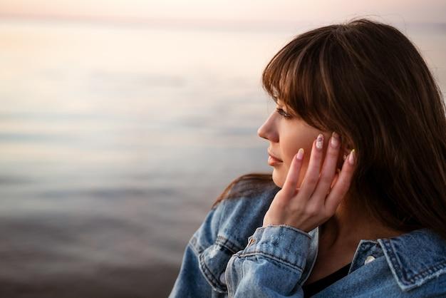 Porträt einer jungen niedlichen frau auf dem hintergrund des meeres bei sonnenuntergang