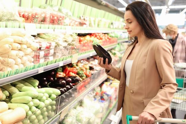 Porträt einer jungen positiven frau, die bio-auberginen im shop kauft