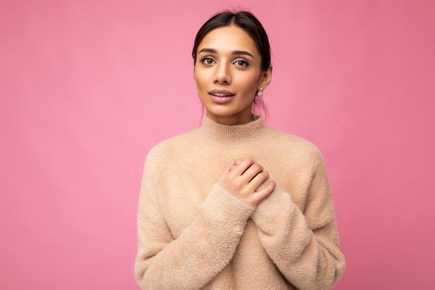 Porträt einer jungen, positiven, hübschen, brünetten frau mit aufrichtigen emotionen, die einen beigefarbenen pullover trägt, einzeln auf rosafarbenem hintergrund mit kopienraum und hand auf der brust haltend Premium Fotos