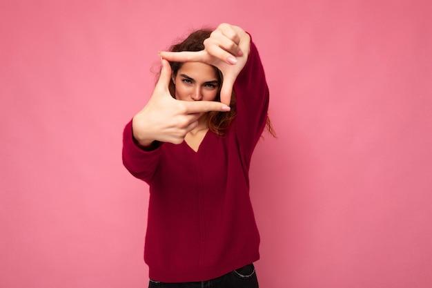 Porträt einer jungen, positiven, hübschen, brünetten, lockigen frau mit aufrichtigen emotionen, die trendiges pink trägt