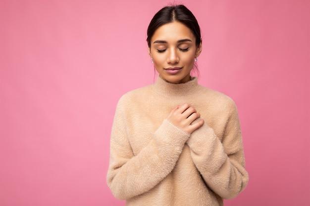 Porträt einer jungen positiven süßen hübschen brünetten frau mit aufrichtigen emotionen, die beige pullover trägt wearing