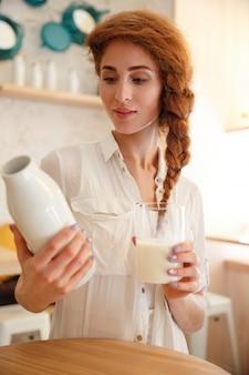 Porträt einer jungen rothaarigen frau, die flasche mit milch hält