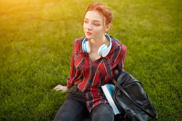 Porträt einer jungen rothaarigestudentin, die musik in den kopfhörern hört