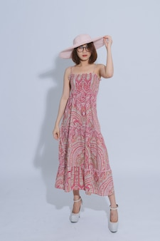 Porträt einer jungen schönen asiatischen frau, die langes kleid in einer hutaufstellung trägt. tragende gläser des kurzen haares des asiatischen mädchens und rosa hut im studio.