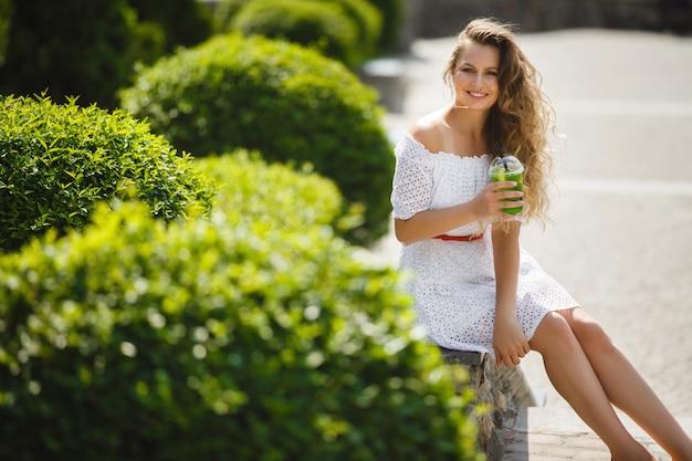 Porträt einer jungen schönen attraktiven frau draußen im sommer mit einem glas eiskaltem saft oder getränk. hübsches mädchen draußen mit frischem mojito