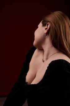 Porträt einer jungen schönen blonden dame, die ein schwarzes, kurzes oberteil mit offenen schultern und eine blaue jeans trägt