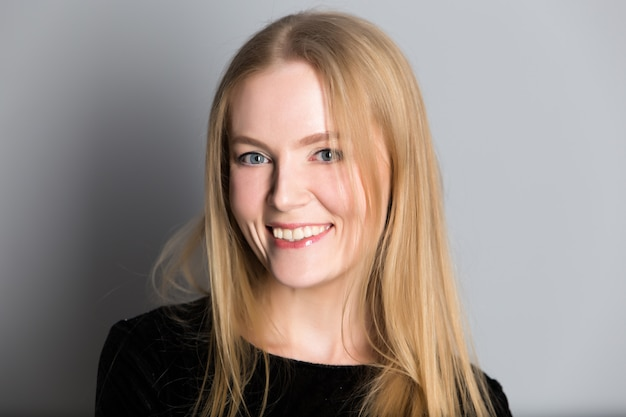 Porträt einer jungen schönen blonden frau mit abendmake-up in einem schwarzen glänzenden kleid nahe einer grauen wand