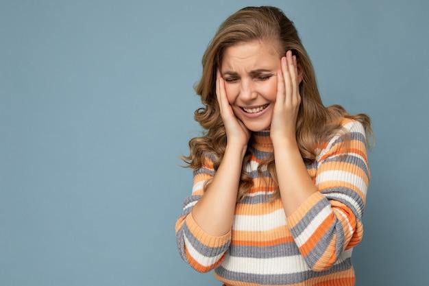 Porträt einer jungen, schönen blonden, lockigen frau mit aufrichtigen emotionen, die einen stilvollen gestreiften pullover trägt, der auf blauem hintergrund mit leerem raum isoliert ist und kopfschmerzen hat. schmerzkonzept