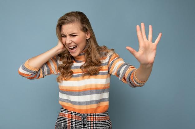 Porträt einer jungen, schönen blonden, lockigen frau mit aufrichtigen emotionen, die einen stylischen gestreiften pullover trägt, der auf blauem hintergrund mit leerem raum isoliert ist und handfläche mit ekelhaftem ausdruck zeigt