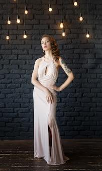 Porträt einer jungen schönen braunen behaarten frau in einem rosa kleid