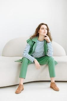 Porträt einer jungen schönen brünetten frau, die auf einem sofa in einem hellen raum sitzt