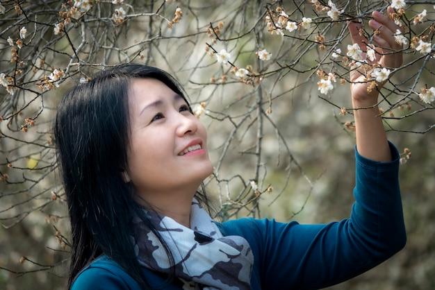 Porträt einer jungen schönen frau, die in einem blühenden garten aufwirft. asiatisches thailand.