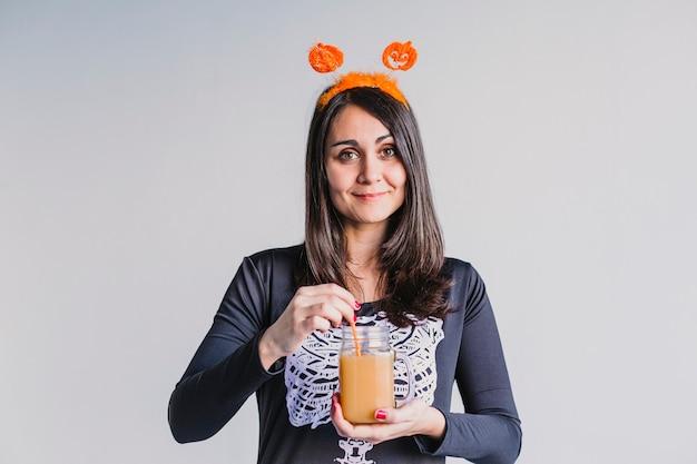 Porträt einer jungen schönen frau, die orangensaft hält. tragen eines schwarz-weißen skelettkostüms. halloween-konzept. drinnen