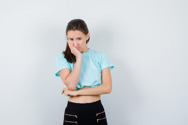 Porträt einer jungen schönen frau, die sich auf die handfläche in t-shirt, hose und nachdenklicher vorderansicht lehnt