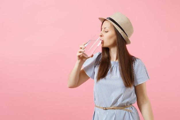 Porträt einer jungen schönen frau in blauem kleid, hut, die klares frisches reines wasser aus glas hält und trinkt, isoliert auf rosafarbenem hintergrund. gesunder lebensstil, menschen, konzept der aufrichtigen emotionen. platz kopieren