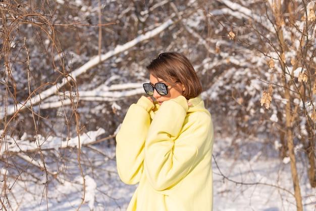 Porträt einer jungen schönen frau in einem verschneiten landschaftswinterwald an einem sonnigen tag, gekleidet in einen gelben großen pullover, mit sonnenbrille, die sonne und schnee genießend