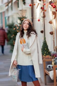 Porträt einer jungen schönen frau in einer baskenmütze in einer europäischen stadt. junge frau hält eine papiertüte mit baguettes. weihnachten. ferien.