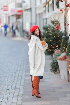 Porträt einer jungen schönen frau in einer roten baskenmütze in einer europäischen stadt. junge frau hält eine papiertüte mit baguettes. weihnachten. ferien.