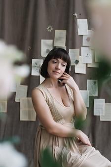 Porträt einer jungen schönen frau mit dunklem haar, das hinter blumen aufwirft