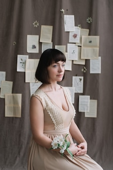 Porträt einer jungen schönen frau mit dunklen haaren und blumen am handgelenk