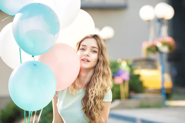Porträt einer jungen schönen frau mit fliegenden bunten luftballons in der stadt