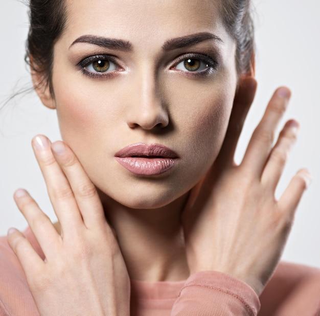 Porträt einer jungen schönen frau mit rauchigen augen make-up. hübsches junges erwachsenes mädchen, das nahes attraktives weibliches gesicht der nahaufnahme aufwirft. hautpflegekonzept