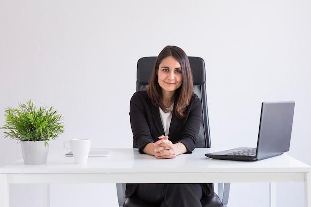 Porträt einer jungen schönen geschäftsfrau, die im büro arbeitet und die kamera betrachtet.
