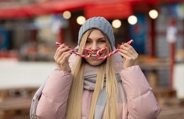 Porträt einer jungen schönen glücklichen frau mit süßigkeiten, die auf der straße einer europäischen stadt aufwirft. weihnachten.