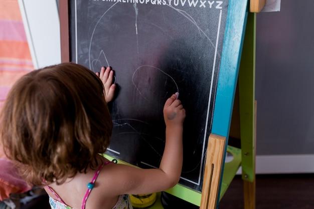 Porträt einer jungen schönen kindermädchenzeichnung auf der tafel zu hause. glück und lebensstil drinnen. sommer