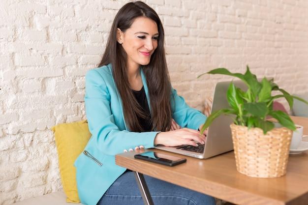 Porträt einer jungen schönheit, die handy in einem restaurant verwendet. sie lächelt. modernes leben eines bloggers mit computerlaptop, -tablette, -notizbuch und -kaffee auf tabelle. freizeitkleidung. lebensstil