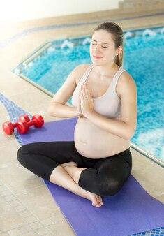 Porträt einer jungen schwangeren frau, die yoga im lotussitz macht doing