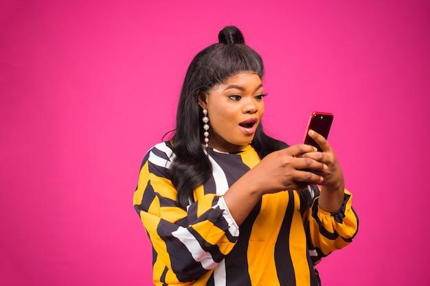 Porträt einer jungen schwarzen afrikanischen fettleibigen frau mit make-up, die ihr handy aufgeregt hält