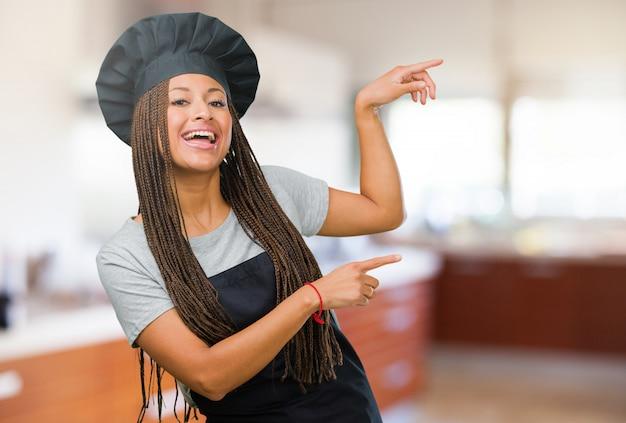Porträt einer jungen schwarzen bäckerfrau, die auf die seite, lächelndes überrascht zeigt, etwas zeigend