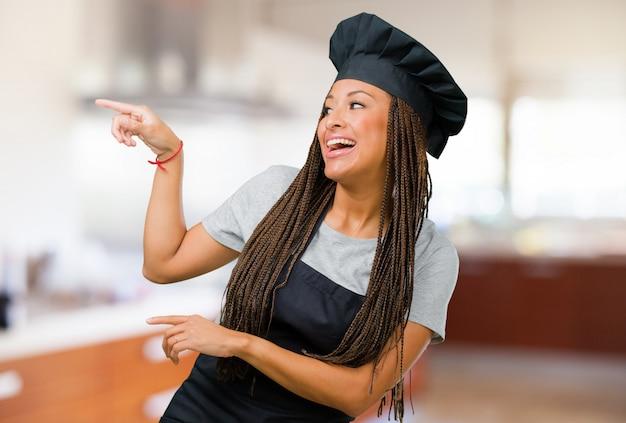 Porträt einer jungen schwarzen bäckerfrau, die auf die seite zeigt