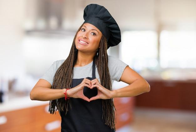 Porträt einer jungen schwarzen bäckerfrau, die ein herz mit den händen macht