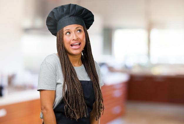 Porträt einer jungen schwarzen bäckerfrau, die oben schaut, an etwas spaß denkt und eine idee hat