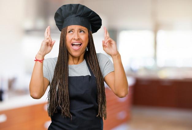 Porträt einer jungen schwarzen bäckerfrau, die seine finger kreuzt, möchte für die zukunft glücklich sein