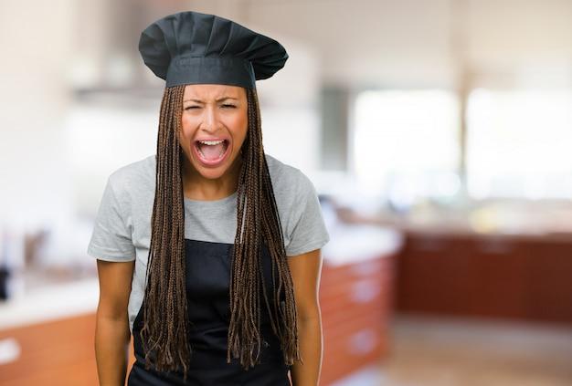 Porträt einer jungen schwarzen bäckerfrau, die verärgert, ausdruck des wahnsinns und geistes herein schreit