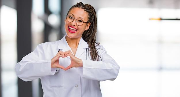 Porträt einer jungen schwarzen doktorfrau, die ein herz mit den händen macht