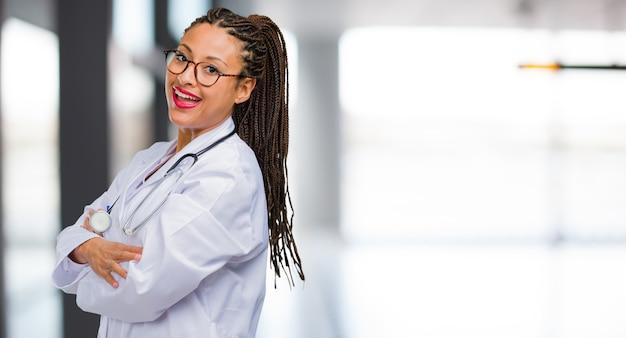 Porträt einer jungen schwarzen doktorfrau, die seine arme kreuzt, lächelt und glücklich