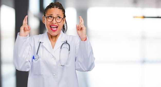 Porträt einer jungen schwarzen doktorfrau, die seine finger kreuzt