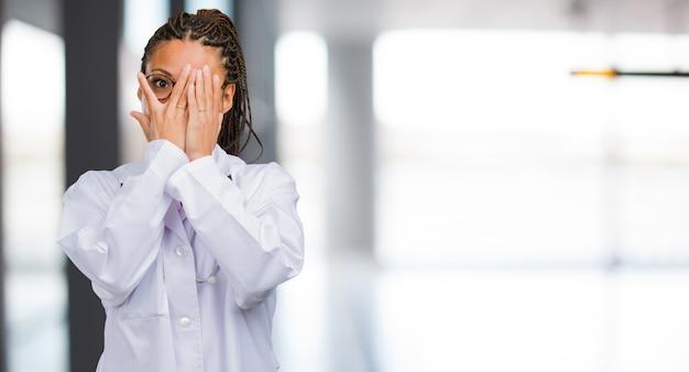 Porträt einer jungen schwarzen doktorfrau fühlt sich besorgt und erschrocken, gesicht, konzept der furcht und angst schauend und bedeckt