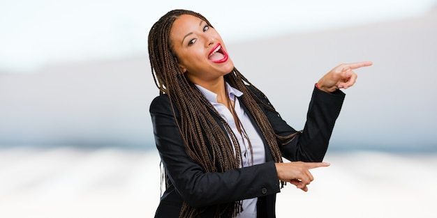 Porträt einer jungen schwarzen geschäftsfrau, die auf die seite zeigt