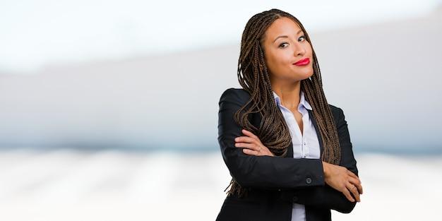 Porträt einer jungen schwarzen geschäftsfrau, die seine arme kreuzt, lächelt und glücklich