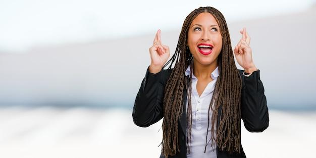 Porträt einer jungen schwarzen geschäftsfrau, die seine finger kreuzt