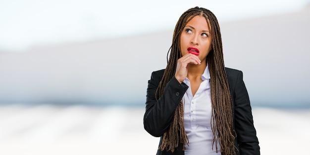 Porträt einer jungen schwarzen zweifelnden geschäftsfrau und verwirrt, an eine idee denkend oder an etwas gesorgt