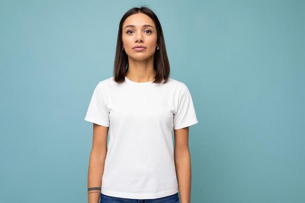 Porträt einer jungen selbstbewussten brünetten frau, die ein trendiges weißes t-shirt mit leerem platz für mock-up trägt. sexy sorglose weibliche person posiert isoliert in der nähe der blauen wand im studio mit freiem platz. modell w