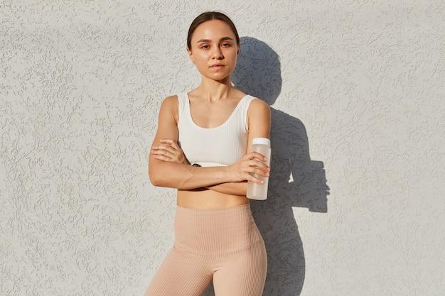 Porträt einer jungen, selbstbewussten, dunkelhaarigen frau mit weißem oberteil und beigefarbenen leggins, die in der nähe der grauen wand im freien steht und eine flasche mit wasser in den händen hält.