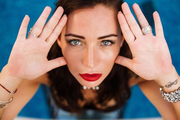 Porträt einer jungen sexy frau, die in einem swimmingpool trägt schwarzen badeanzug aufwirft