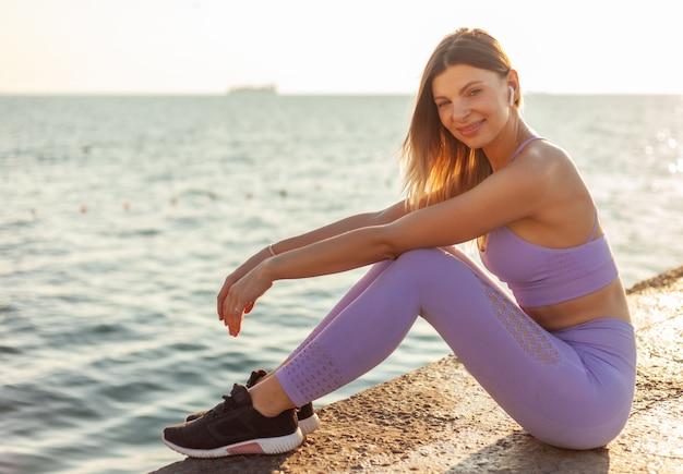 Porträt einer jungen sportfrau bei sonnenaufgang am strand. junge fit frau genießt musik in kopfhörern